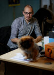 Photo of James Merchant with a dog on his desk